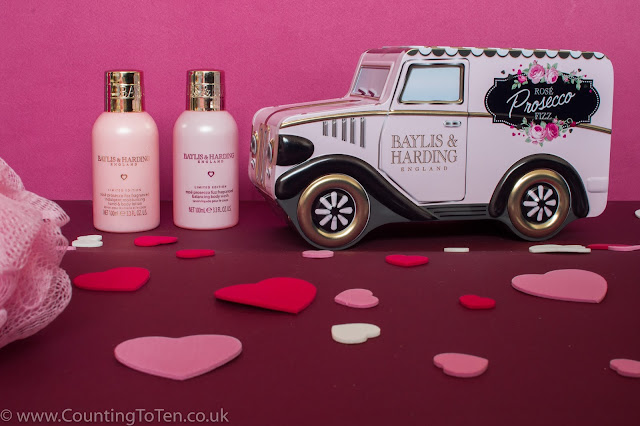 A metal van shaped tin, 2 mini pink bottles and a body polisher with hearts in the forground