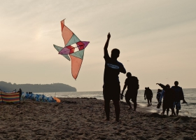 Flying a kite on the beach.