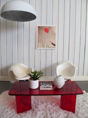 Modern dolls' house miniature scene with white paneled walls, concrete floor with a white flokati rug on top. Two white Eames chairs sit behind a red perspex coffee table and a large white light hangs overhead.