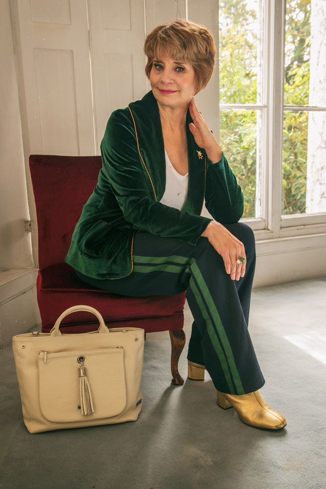 Image showing a 40 plus woman in green velvet jacket and navy side stripe trousers with a cream convertible bag