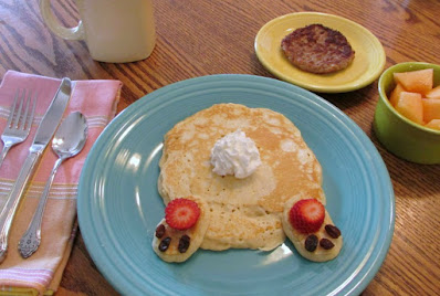 bunny butt pancake on blue plate with a small bowl of melon and sausage patty
