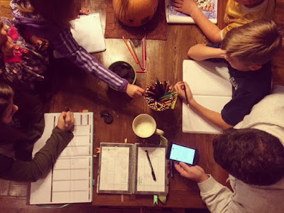 Family gathered around the table planning out their week Mormon Mom Planner