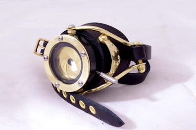 Steampunk monocle or cyclops goggle (eyepatch) made of brass and leather with a brass aperture shutter from a camera.