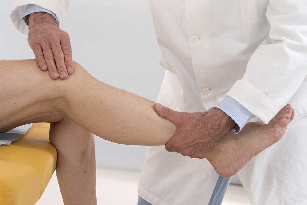 A doctor examines a patient's knee