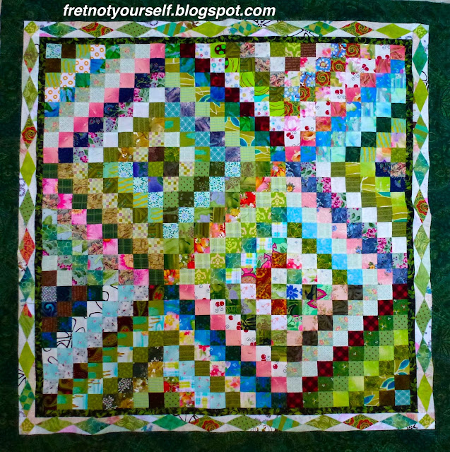 Scrappy Trip quilt made of mainly greens and pinks.