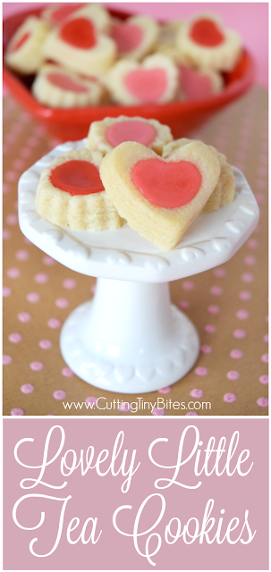 Sweet heart shaped tea cookies for Valentine's Day. Melt in your mouth buttery shortbread with a dab of sweet pink frosting in the center! Perfect for class parties or a tea party!