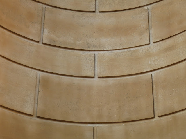 Wall made from large, curved rectangles of different sizes in pale stone