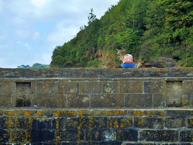 Girl on sea wall at Charlestown Harbour, Cornwall