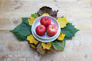 Three apples in a bowl surrounded by fall leaves on a weathered wood table
