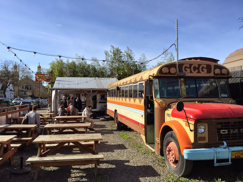 Outdoor and indoor seating in an old school bus at The Grilled Cheese Grill