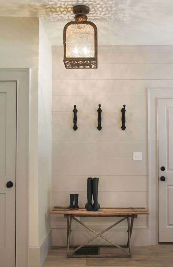 Modern farmhouse entry way with shiplap, wood bench, lantern, and wellies