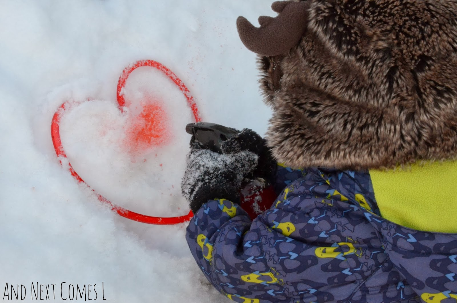 Spray painting hearts in the snow for Valentine's Day from And Next Comes L