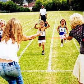 Niños corriendo y madres alentándolos a terminar.