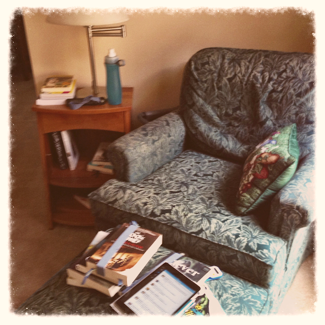 armchair by a window surrounded by books on side table and ottoman