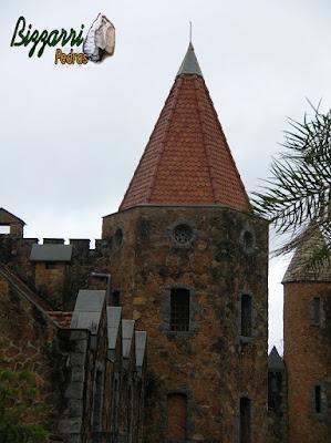 Torre de pedra construída com pedra moledo na cor meio avermelhada com espessura de 20 cm a 30 cm.