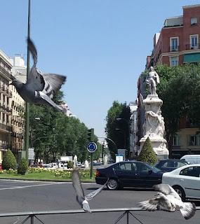 La estautua y su gran pedestal con relieves están tallados sobre roca blanca y se alza sobre un jardín.