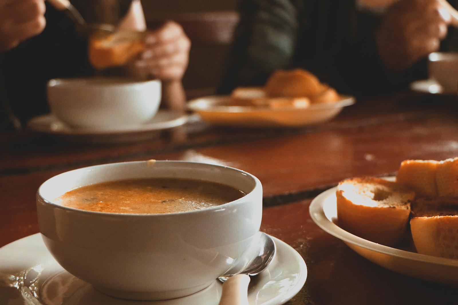mesa com sopa de milho e pães