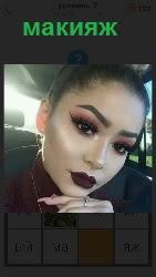 сидит девушка у которой на лице сделан макияж