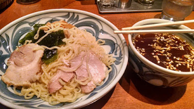 A bowl with pork and noodles, and a bowl with sauce.