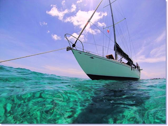 Vintage sailboat anchored in swirling translucent turquoise seas of Bimini Bahamas.