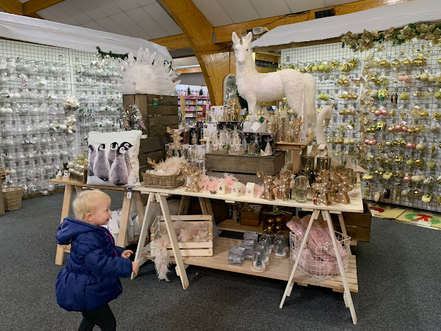 A toddler looking at a display of Christmas decorations