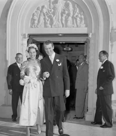 Photo of Jimmy Stewart and wife Gloria outside church after their August 9, 1949 wedding
