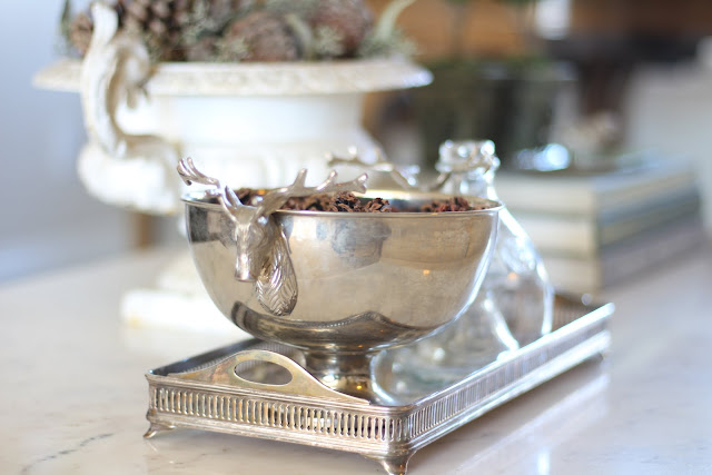 styling a coffee table silver bowl deer heads pinecones christmas