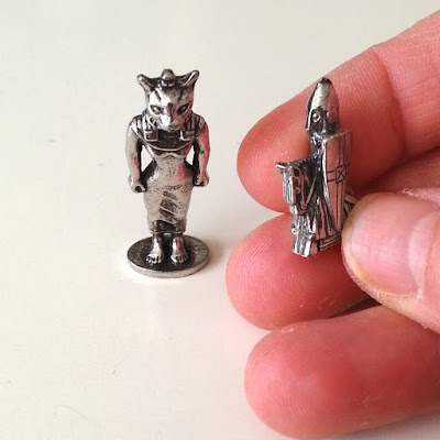 Small metal ornamental Egyptian cat figure and a small metal knight figure on a horse.