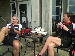 Two cyclists enjoying a break and having a coffee.