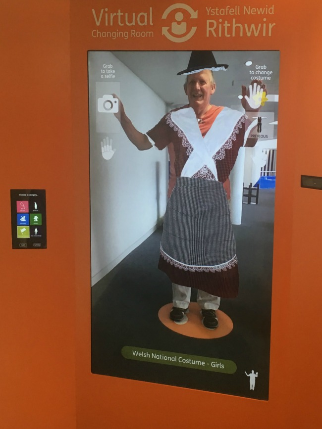 Techniquest-Virtual-Reality-changing-room-a-toddler-explores-an-image-of-a-man-in-Welsh-womans-national-costume