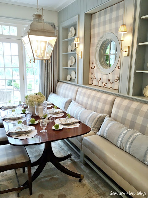 Blue and white check banquette in breakfast area with built-in shelves