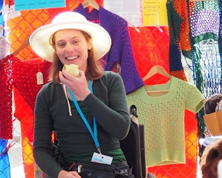 Jodie is seated, smiling with an apple in her hand. Behind her are garments hanging on the fence. From left to right, red beaded crochet lace top and belt, purple lace stitch cardigan, green 'petal pullover' short sleeved crocheted top, 'Woodstock duster jacket' in blue, green, orange and purple crochet mesh.