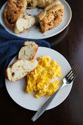 slices of bacon cheddar bread on a plate with scrambled eggs with the remaining wreath of bread in the background