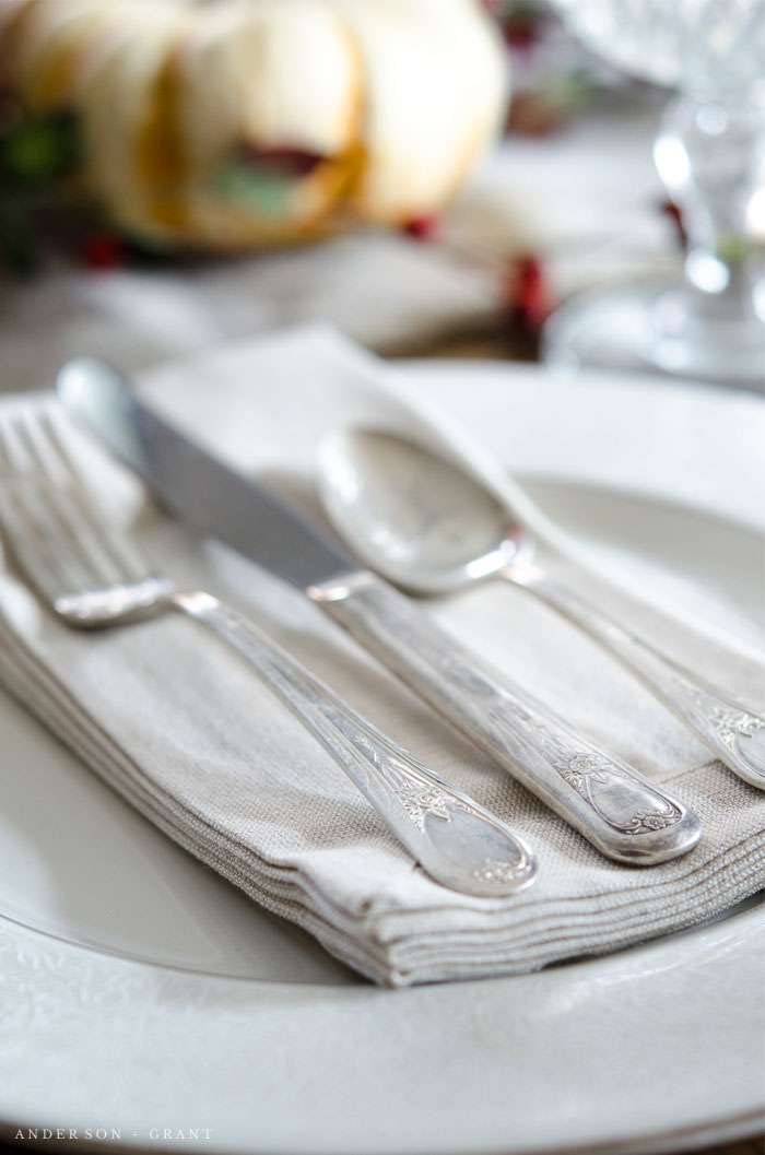 Antique silverware layered on a linen napkin.  |  www.andersonandgrant.com