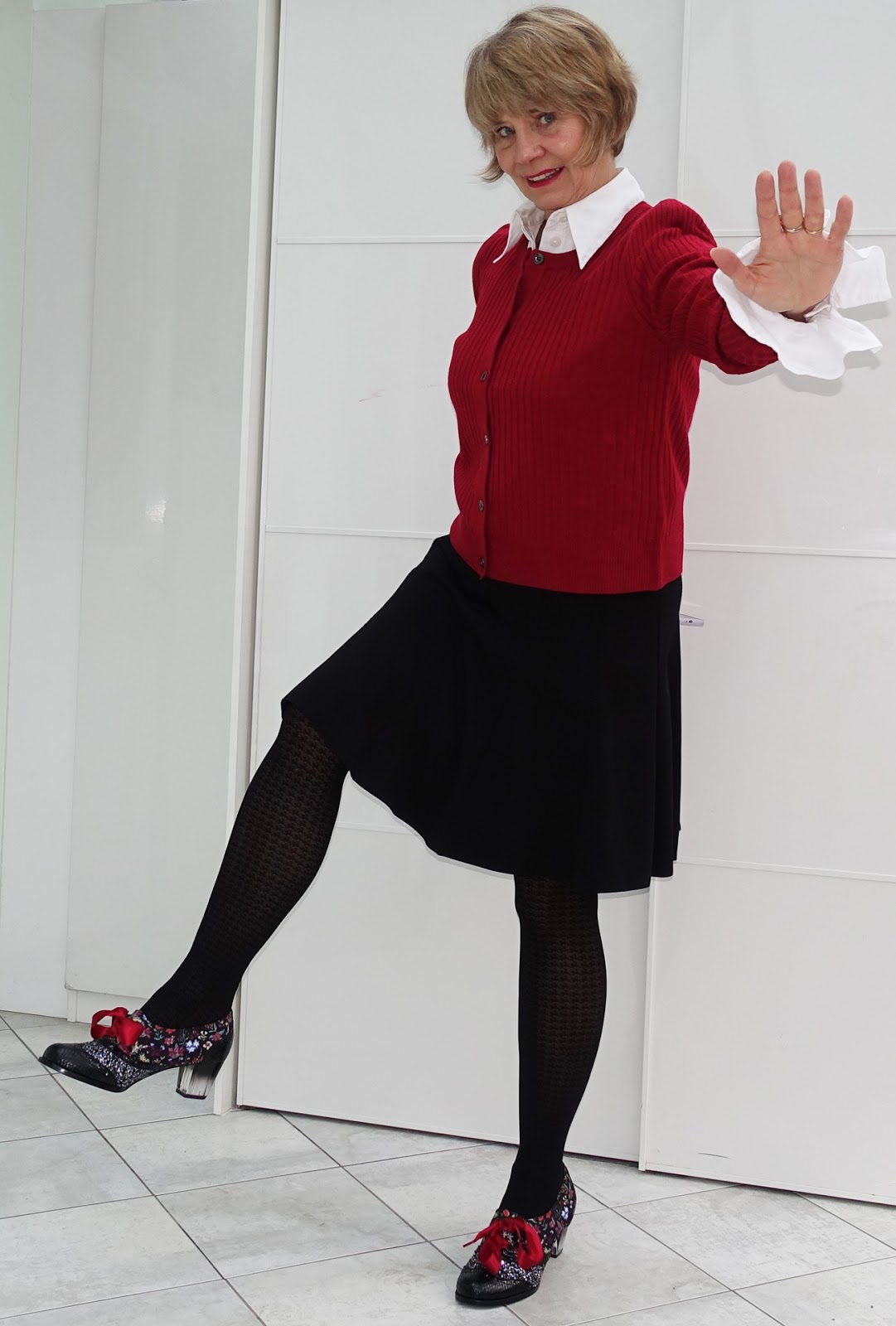 Image shwing a woman wearing a red cardigan with black and an attention grabbing pair of shoes with red ribbons and perspex heels