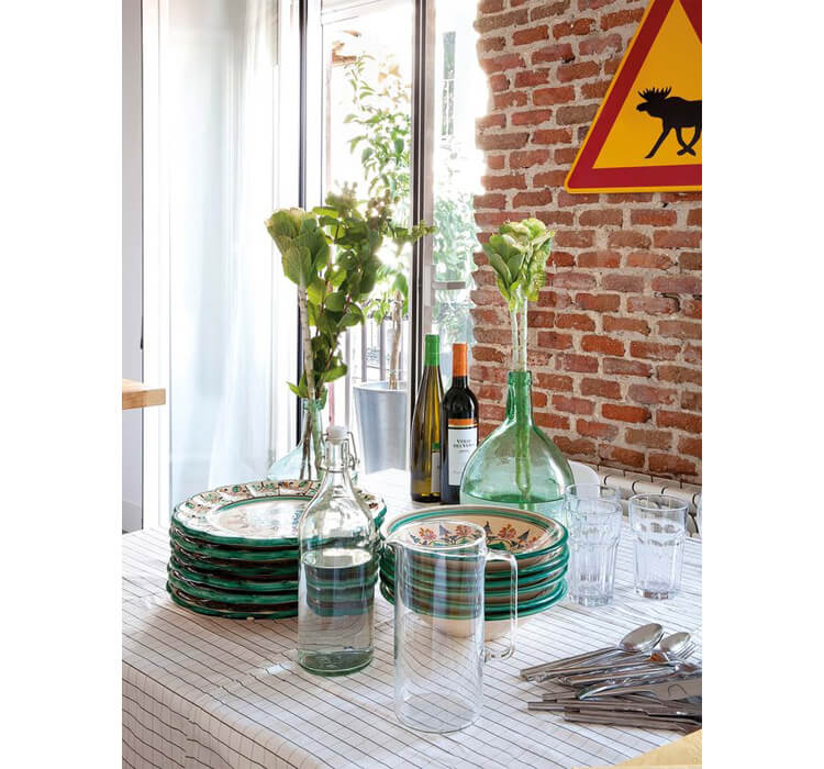 Tavola apparecchiata in una sala da pranzo con parete di mattoni a vista