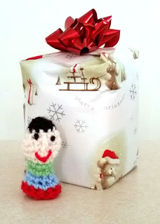 A wrapped Christmas gift with a red bow on top has a small simple finger puppet standing in front of it. The puppet has black hair, black dot eyes, a red smile and stripes on the body, from neck to bottom edge: green, blue red.