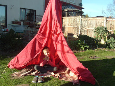 Photo of a little boy sitting cross-legged in a homemade tent on a small lawn
