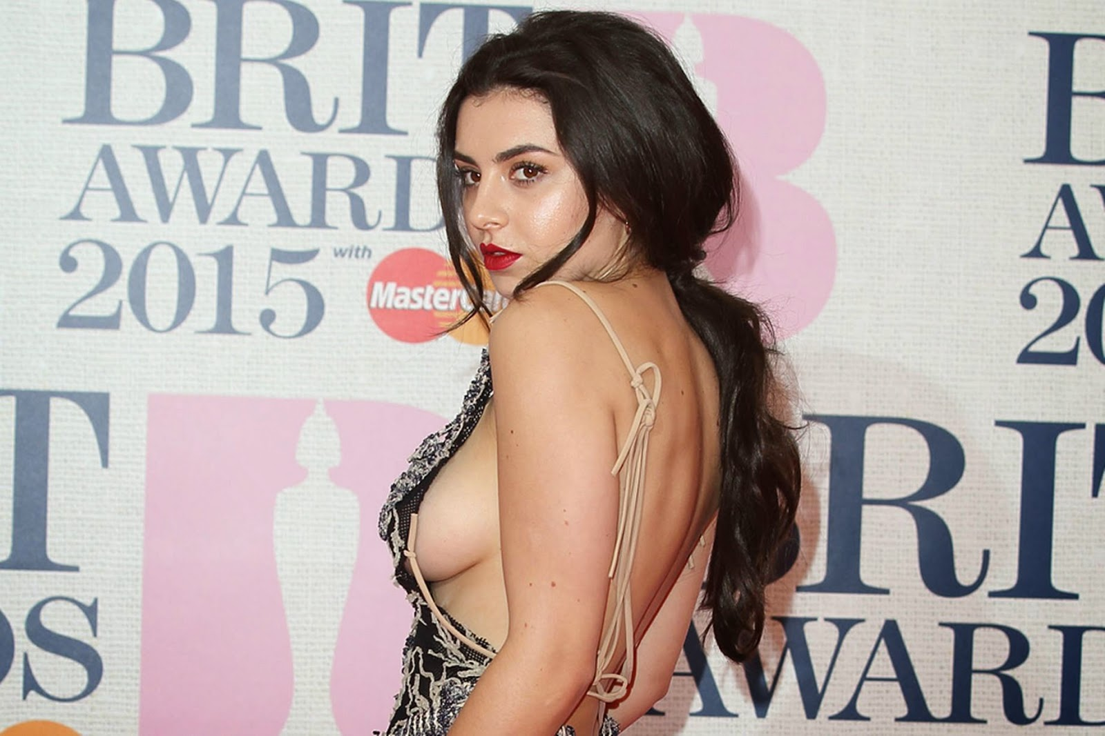 Charli XCX in a backless monochrome dress at the 2015 BRIT Awards in London