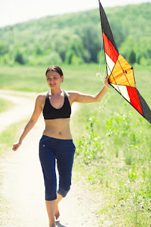 Photo of a Woman Holding a Kite While Walking on a Country Lane in the Summer