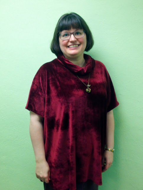 Person standing in front of blank wall showing off velour tunic