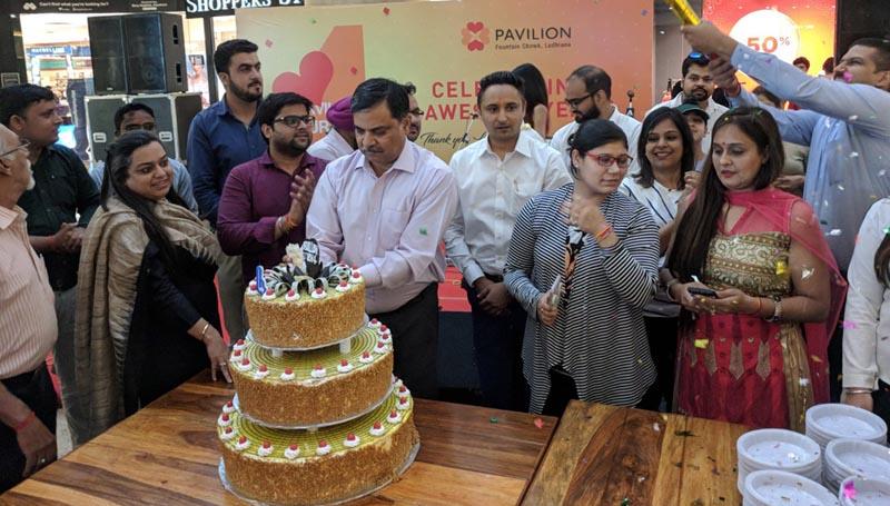 पैविलियन मॉल के अधिकारी मॉल की चौथी वर्षगांठ के अवसर पर केक काटते हुए