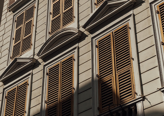 yellow and grey building in genova, italy with shadows and tradional shutters