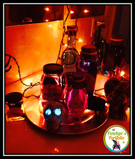 Various sized bottles with Halloween lables on them to resemble potions, pictured in the dark, with halloween lights