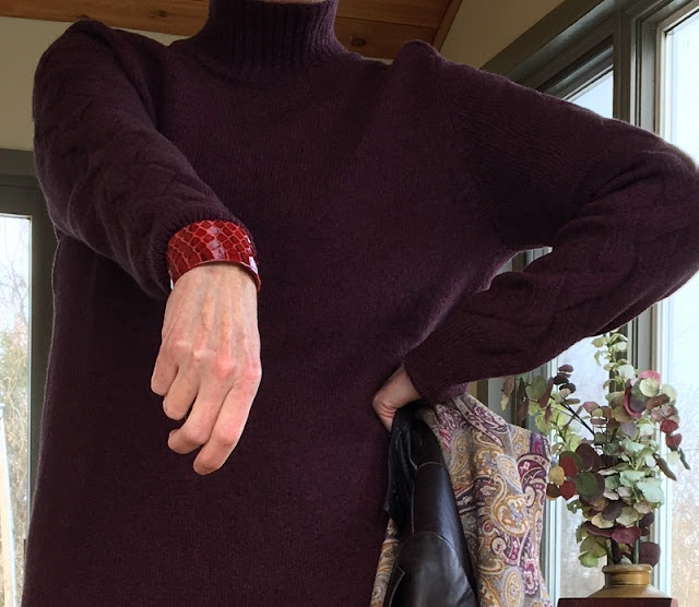 woman in burgundy sweater showing a burgundy and red wrist cuff