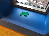 one green flannel sheep next to low window