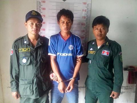 A man poses for a photo with authorities at a Kep police station after he was arrested for the murder of a 6-year-old girl. CPU