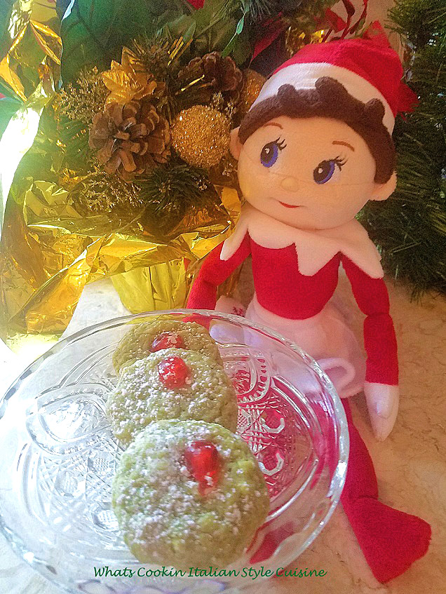 these are a festive macadamia nut green cookie with cherries on top with the elf on the shelf female doll in the photo along with pine cone centerpiece.