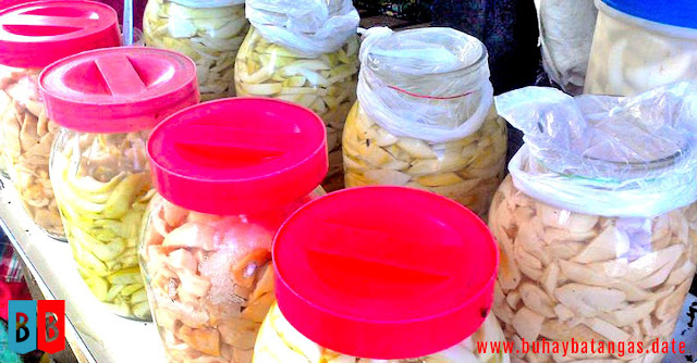Buro jars at a stall in a public market.