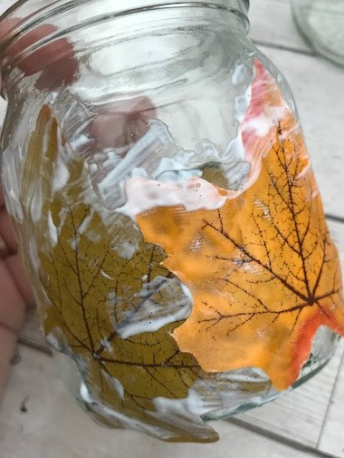 Leaves being glued to a jar